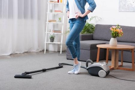 Photo for Partial view of woman standing akimbo in room wit vacuum cleaner - Royalty Free Image