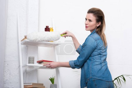 Photo for Side view of woman in casual clothing with dust cleaning brush cleaning home - Royalty Free Image