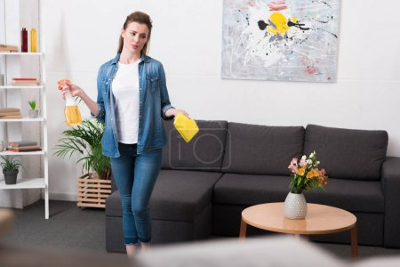 tired woman with cleaning supplies in hands standing in room at home
