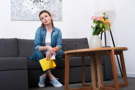 Photo for Tired woman with cleaning supplies in hands resting on sofa at home - Royalty Free Image