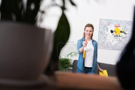 selective focus of smiling woman with rag and detergent at home