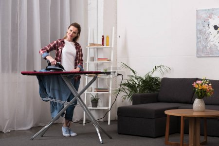 Photo for Attractive woman ironing clothing at home - Royalty Free Image