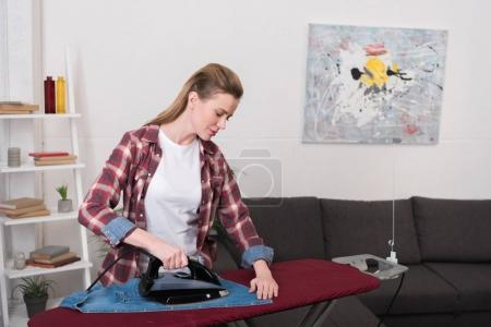 portrait of attractive woman ironing clothing at home