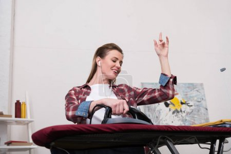 low angle view of smiling woman listening music while ironing clothes at home