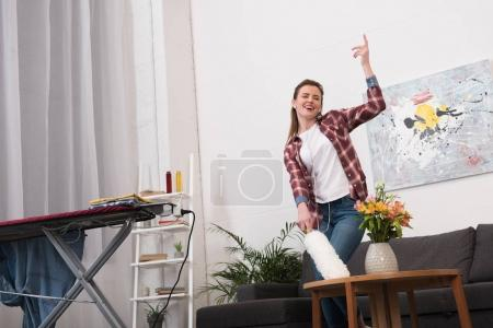 Photo for Woman with dust cleaning brush listening to music while cleaning home - Royalty Free Image