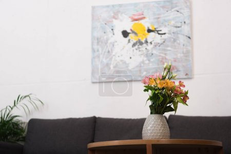 close up view of flowers in vase on wooden coffee table