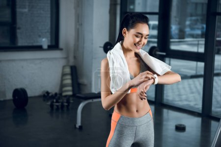 young happy sportswoman using smartwatch to check activity at gym