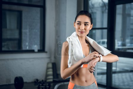 young sporty woman using smartwatch to check activity at gym