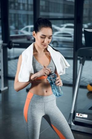 young sporty woman with water bottle and towel on shoulders at gym