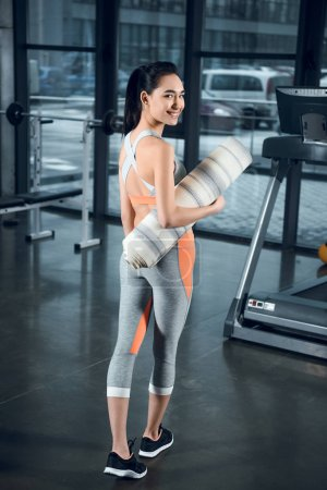 young fit woman with rolled yoga mat at gym