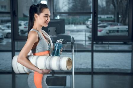 young athletic woman with rolled yoga mat and water at gym