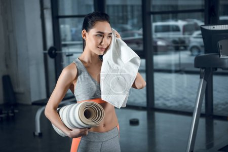 young sporty woman with rolled yoga mat wiping sweat with towel after exercises at gym