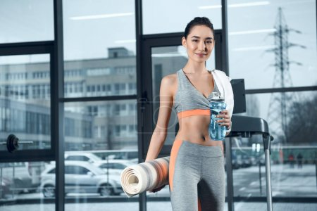 young sporty woman with rolled yoga mat and water at gym