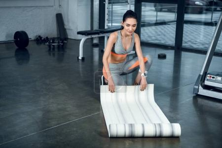 attractive young woman rolling yoga mat after exercises at gym