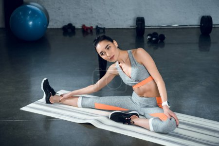 young sporty woman doing side bend on yoga mat at gym