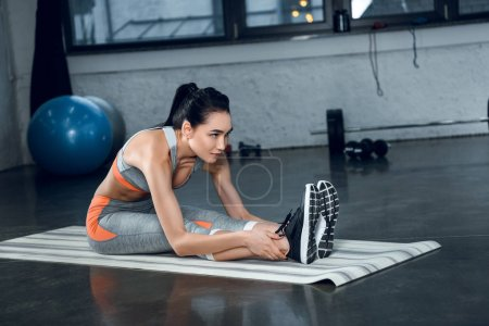 young sporty woman doing forward bend on yoga mat at gym