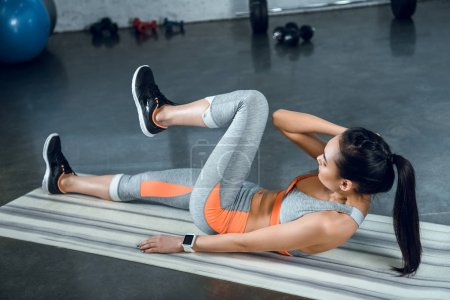 young sporty woman doing side crunches on yoga mat at gym