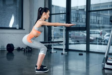 Photo for Young sporty woman doing squats with outstretched hands at gym - Royalty Free Image