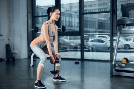 Photo for Young sporty woman doing squats with weight plates at gym - Royalty Free Image