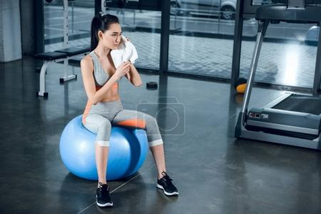 young sporty woman relaxing on fitball at gym