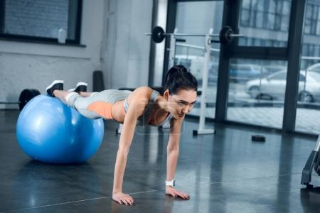 young sporty woman doing plank with legs on fitball at gym