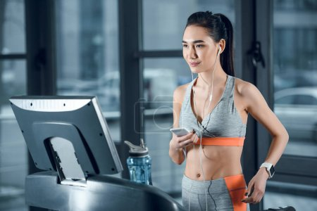 Photo for Young athletic sportswoman using smartphone on treadmill at gym - Royalty Free Image