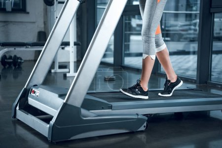 cropped shot of sportswoman running on treadmill at gym