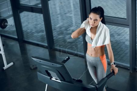 high angle view of young athletic sportswoman wiping with towel after jogging on treadmill at gym