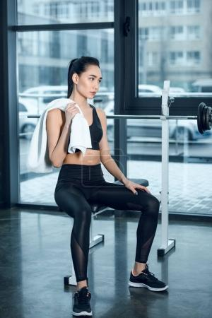 young sporty woman relaxing on workout bench with towel at gym