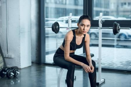 young sporty woman sitting on workout bench at gym