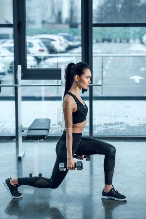 Photo pour Vue latérale de la jeune femme fit faire seule jambe squats avec haltères au gymnase - image libre de droit