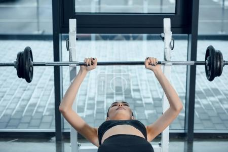 young fit woman lifting barbell while lying on bench at gym