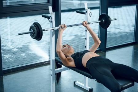 young athletic woman lifting barbell while lying on bench at gym