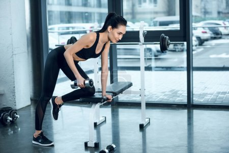 young sporty woman lifting dumbbell while leaning on workout bench at gym