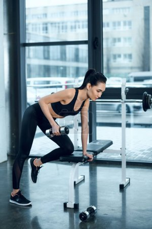 young fit woman lifting dumbbell while leaning on workout bench at gym