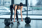 young athletic woman doing deadlifting at gym