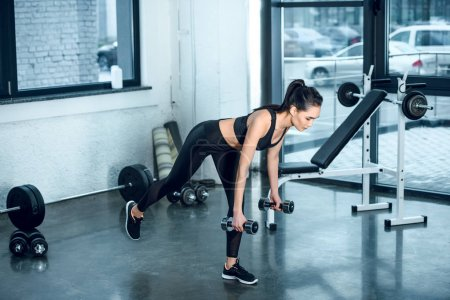 young sporty woman working out with barbells at gym