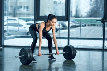 young athletic woman lifting barbell at gym