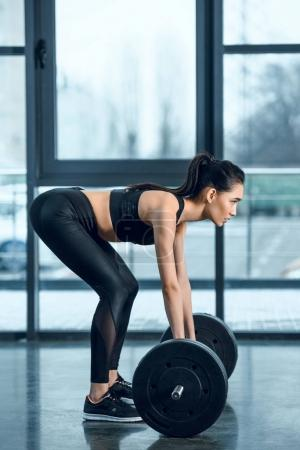 side view of young athletic woman lifting barbell at gym