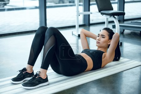 young sporty woman doing crunches on yoga mat at gym