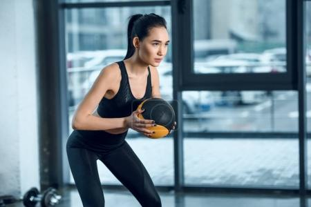 young sporty woman exercising with ball at gym