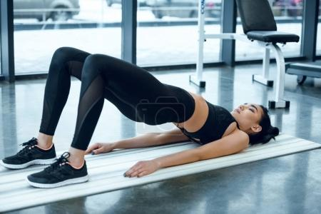 Photo for Young sporty woman doing bridge exercise on yoga mat at gym - Royalty Free Image