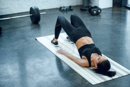 young sporty woman doing bridge exercise at gym