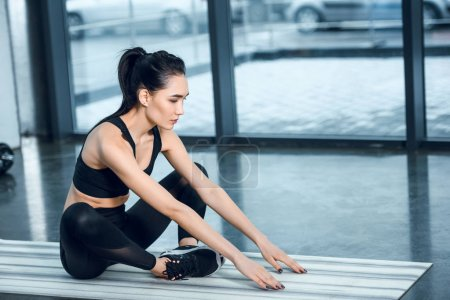 young athhletic woman stretching on yoga mat at gym