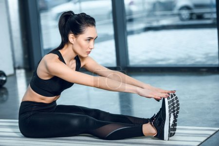 young sporty woman stretching and reaching for feet with hands on yoga mat at gym