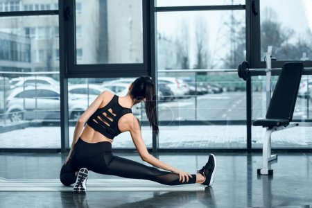Photo for Back view of athletic woman stretching leg on yoga mat at gym - Royalty Free Image