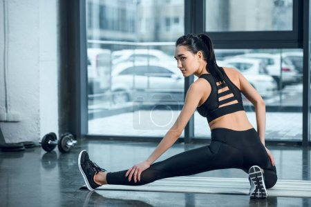 young athletic woman stretching leg on yoga mat at gym