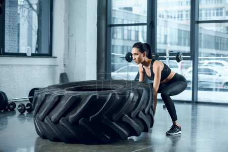 young athletic woman flipping workout wheel at gym