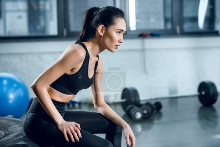 side view of attractive fit woman sitting on workout wheel after training at gym