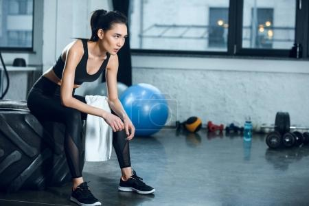 young fit woman sitting on workout wheel after training at gym
